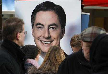 Pedestrians are pictured in front of an election campaign poster of Lower Saxony's state governor and Christian Democratic top candidate David McAllister (CDU) in Hanover January 19, 2013. State elections in Lower Saxony will be held on January 20. REUTERS/Fabrizio Bensch