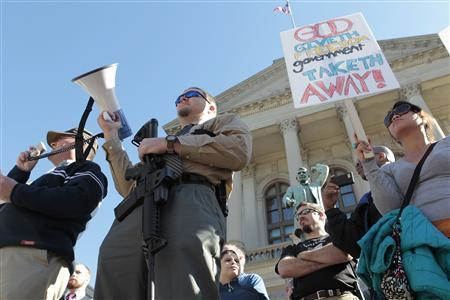 Michael Rugh (2nd-L) holds a AR-15 rifle as he participates along with David Mace (L) and Luchie Wooten (R), during the Guns Across America pro-gun rally at the State Capitol in Atlanta, Georgia, January 19, 2013. REUTERS/Tami Chappell