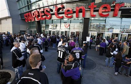 A Staples Center employee hugs a Los Angeles Kings fan as fans return for the first NHL game of the Kings' season against the Chicago Blackhawks in Los Angeles, California, January 19, 2013. REUTERS/Lucy Nicholson