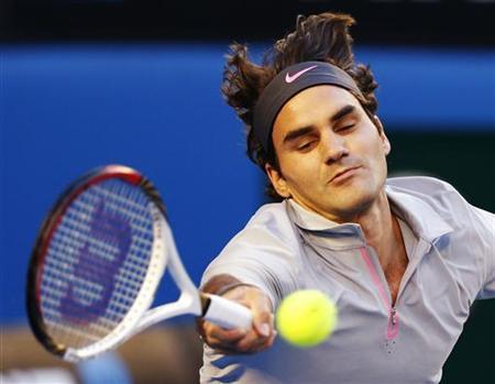 Roger Federer of Switzerland hits a return to Bernard Tomic of Australia during their men's singles match at the Australian Open tennis tournament in Melbourne January 19, 2013. REUTERS/Daniel Munoz