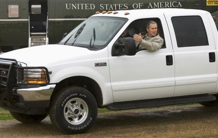 Then U.S. President George W. Bush leans out of his pickup truck's window to speak to the press as he rides with Russian President Vladimir Putin at the Bush ranch in Crawford, Texas in this November 14, 2001 file photo. REUTERS/Win McNamee/Files