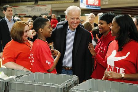 U.S. Vice President Joe Biden (C) greets volunteers as he arrives to help assemble care kits for U.S. military service members and veterans at a Unite America in Service event at the National Guard Armory in Washington, January 19, 2013. REUTERS/Jonathan Ernst