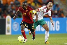 Le Marocain Karim El Ahmadi (à droite), à la lutte avec l'Angolais Mingo Bille, samedi à Soweto lors d'une rencontre du groupe A de la phase de poules de la Coupe d'Afrique des nations. Les deux équipes se sont séparées sur un match nul 0-0. /Photo prise le 19 janvier 2013/REUTERS/Siphiwe Sibeko