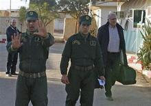 Des gendarmes algériens escortent un otage norvégien libéré au poste de police d'In Amenas, samedi. Selon le ministre algérien de la Communication, Mohamed Said, plus de 23 otages ont été tués lors de la prise d'otages qui a pris fin samedi dans le complexe gazier de Tiguentourine, dans le sud-est de l'Algérie mais le bilan final, qui devrait être communiqué dans les prochaines heures, devrait être plus lourd. /Photo prise le 19 janvier 2013/REUTERS/Louafi Larbi