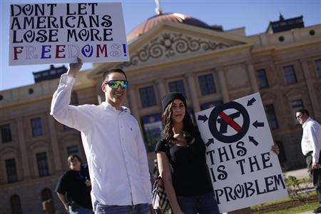 A demonstrator (L), who supports the second amendment, and a woman, who is against guns and the second amendment, hold signs outside the Arizona State Capitol in Phoenix, Arizona January 19, 2013. REUTERS/Joshua Lott