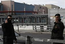 Police officers secure an area near a shopping mall (seen in the background) following an explosion near Athens January 20, 2013. REUTERS/John Kolesidis