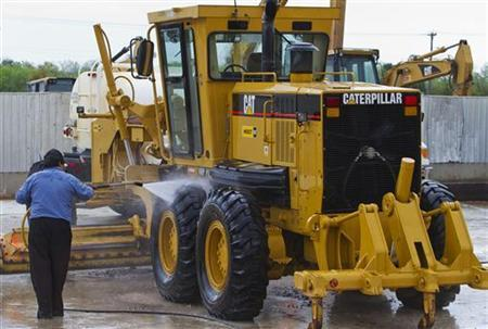 A worker washes a road grader at Holt Caterpillar, the largest Caterpillar dealer in the United States, in San Antonio, Texas March 19, 2012. REUTERS/Richard Carson