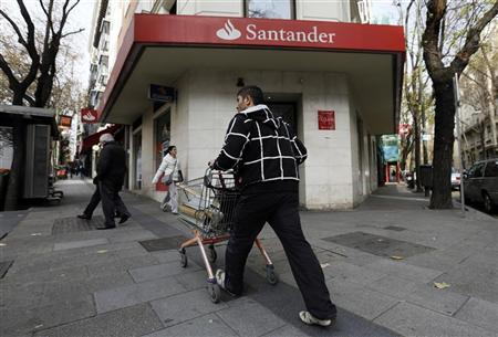 A man with a trolley walks past a Santander bank branch in Madrid December 17, 2012. REUTERS/Andrea Comas