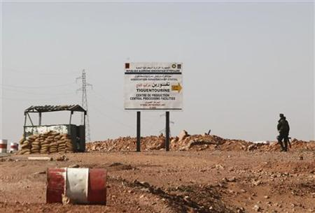 An Algerian soldier stands at a checkpoint near a road sign indicating 10 km (6 miles) to a gas installation in Tigantourine (sometimes spelled Tiguentourine), the site where Islamist militants have been holding foreigners hostage according to the Algerian interior ministry, in Amena January 19, 2013. REUTERS/Ramzi Boudina