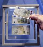 Peter Praet, miembro del Consejo Ejecutivo del Banco Central Europeo (BCE), advirtió de que la economía de la zona euro sigue debilitándose, por lo que es necesario que los estados del bloque continúen con sus reformas. En la imagen, un periodista compara un billete nuevo de cinco euros con uno antiguo en Fráncfort el 10 de enero de 2013. REUTERS/Kai Pfaffenbach