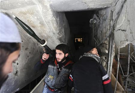 Fighters from Fateh al Sham unit of the Free Syrian Army enter a house in Haresta neighbourhood of Damascus January 20, 2013. REUTERS/Goran Tomasevic