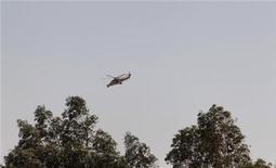 Hélicoptère algérien survolant In Amenas. Les responsables français ont prôné dimanche une fermeté implacable face au terrorisme et justifié l'attitude d'Alger dans le dénouement sanglant de la prise d'otages du site gazier d'In Amenas, au Sahara. /Photo prise le 19 janvier 2013/REUTERS/Louafi Larbi