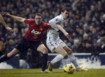 Gareth Bale de Tottenham (à droite) accroche le Mancunien Phil Jones. Manchester United, leader de la Premier League, a concédé dimanche le match nul 1-1 en toute fin de rencontre face à Tottenham, qui a marqué dans le temps additionnel par Clint Dempsey. /Photo prise le 20 janvier 2013/REUTERS/Dylan Martinez