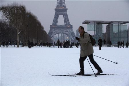 A man uses cross-country skis to make his way across the snow-covered Champs de Mars near the Eiffel Tower in Paris January 20, 2013. Several inches of snow fell in the French capital halting some transportation and closing some public parks. REUTERS/John Schults