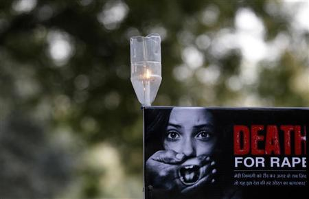 A candle is seen on a placard during a protest in New Delhi December 29, 2012. REUTERS/Adnan Abidi