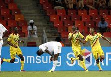 Seydou Keita (à droite) célèbre avec ses coéquipiers un but face au Niger. Il a fallu attendre ce but du capitaine malien à la 84e minute du match Mali-Niger (1-0) pour assister dimanche à une première victoire lors de la Coupe d'Afrique des nations (CAN) 2013 en Afrique du Sud après trois matches nuls consécutifs. /Photo prise le 20 janvier 2013/REUTERS/Siphiwe Sibeko