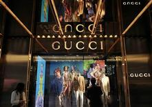 A man watches in front of a window display outside a Gucci store at Tsim Sha Tsui shopping district in Hong Kong January 17, 2013. REUTERS/Bobby Yip