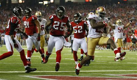 San Francisco 49ers running back Frank Gore (R) scores a touchdown past Atlanta Falcons strong safety William Moore (25) during the fourth quarter in the NFL NFC Championship football game in Atlanta, Georgia January 20, 2013. REUTERS/Chris Keane