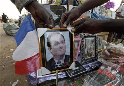 Malians display a picture of French President Francois Hollande for sale at a market in Bamako January 20, 2013. French troops in armoured vehicles advanced on Sunday towards a central Malian town abandoned by Islamist rebels after days of air strikes, moving cautiously for fear of guerrilla-style counterattacks by the al Qaeda-linked fighters. REUTERS/Eric Gaillard