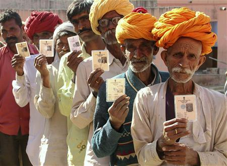 Villagers pose with their identity cards as they stand in line to open a bank account at a camp organised by a private bank in a village at Ajmer in the desert Indian state of Rajasthan, January 10, 2013. REUTERS/Stringer