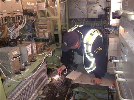NTSB Investigator Mike Bauer examines the inside of a Boeing 787 under investigation at Boston's Logan International Airport in this January 8, 2013 handout photo. REUTERS/NTSB/Handout
