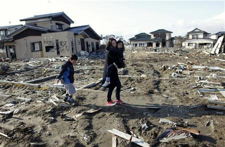 Wakana Kumagai, 7, carried by her mother Yoshiko and followed by her brother Koki visit the spot where their house, which was washed away by the March 11, 2011 tsunami, used to stand in Higashimatsushima, Miyagi prefecture March 11, 2012, to mark the first anniversary of an earthquake and tsunami that killed thousands and set off a nuclear crisis. REUTERS/Toru Hanai