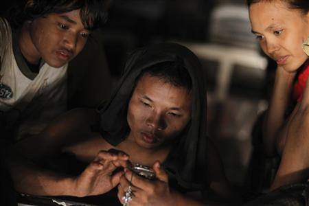 Workers use their mobile phone in a vehicle on their way home in Yangon January 18, 2013. REUTERS/Soe Zeya Tun