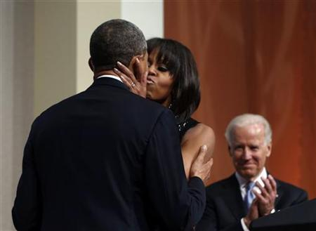 U.S. President Barack Obama is kissed by first lady Michelle Obama at an inaugural reception at the National Building Museum in Washington January 20, 2013. Seen at right is Vice President Joseph Biden. REUTERS/Larry Downing