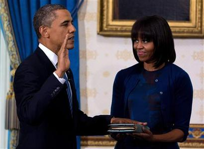 U.S. President Barack Obama takes the oath of office as frst lady Michelle Obama holds a bible during the official swearing-in ceremony at the White House in Washington January 20, 2013. REUTERS/Doug Mills/Pool