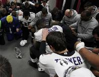 Baltimore Raven players pray in the dressing room around the AFC Championship Trophy after defeating the New England Patriots in the NFL AFC Championship football game in Foxborough, Massachusetts, January 20, 2013. REUTERS/Jim Young