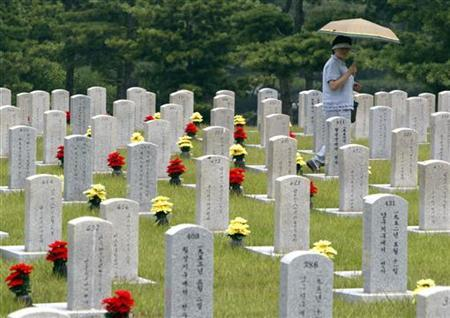 A woman looks at the national cemetery in Seoul June 23, 2006. REUTERS/You Sung-Ho/Files