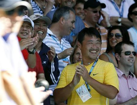 The husband and coach of Li Na of China, Jiang Shan, celebrates after she won her semi-final match against Caroline Wozniacki of Denmark at the Australian Open tennis tournament in Melbourne January 27, 2011. REUTERS/Tim Wimborne