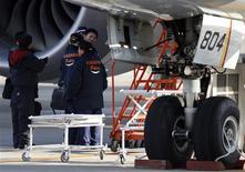 Enquêteurs japonais auprès d'un 787 de la compagnie All Nippon Airways; sur la tarmac de l'aéroport de Takamatsu. Le ministère japonais des Transports va enquêter sur la société fabriquant les batteries au lithium-ion du 787 Dreamliner de Boeing, conjointement avec l'autorité de l'aviation civile américaine (FAA). /Photo prise le 18 janvier 2013/REUTERS/Issei Kato