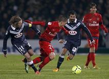 Marco Verratti du PSG (au centre) pris en tenailles par les Bordelais Jaroslav Plasil (à gauche) et Fahid Ben Khalfallah, sur la pelouse du stade Chaban-Delmas. Sans vraiment briller à Bordeaux (1-0), le Paris Saint-Germain a retrouvé de peu dimanche la seule place qui sied à ses ambitions en Ligue 1, la première. Le classement se joue à presque rien, puisque le PSG et Lyon, 42 points chacun, se départagent à la différence de buts. /Photo prise le 20 janvier 2013/REUTERS/Régis Duvignau