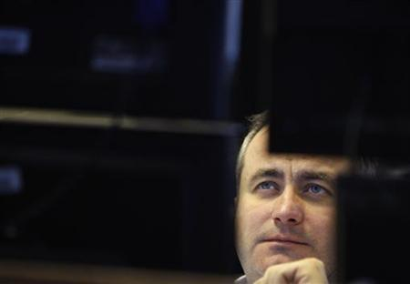 A currency trader reacts at his desk in the dealing room of a brokerage in Budapest November 25, 2011. REUTERS/Bernadett Szabo/Files