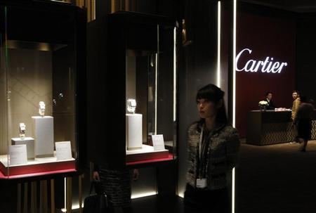 A visitors looks at the Cartier booth during the 'Salon International de la Haute Horlogerie' at Palexpo in Geneva January 17, 2012. REUTERS/Ruben Sprich