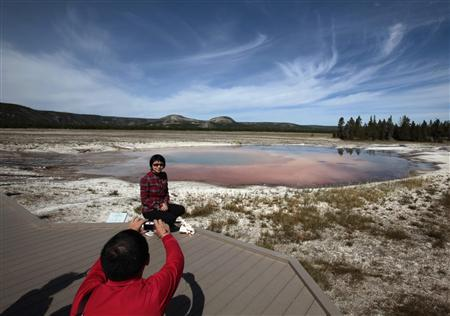 A tourist poses for a photo in front of a spring in Yellowstone National Park, Wyoming in this August 13, 2011, file photo. REUTERS/Lucy Nicholson/Files