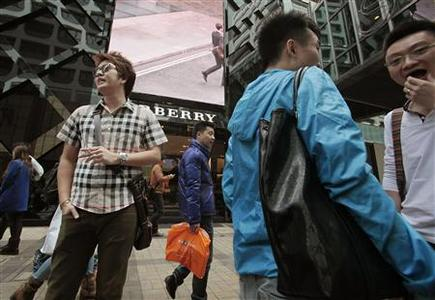 Mainland Chinese visitors stand outside a Burberry store at Tsim Sha Tsui shopping district in Hong Kong January 18, 2013. REUTERS/Bobby Yip