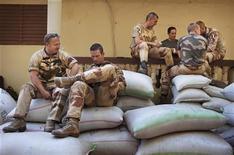 Una columna de vehículos blindados con personal francés y maliense y camiones de suministro avanzaron hacia el norte hasta la ciudad de Diabaly, en el centro de Mali, después de que los rebeldes islamistas que la controlaban se desvanecieran, dijeron fuentes de seguridad. En la imagen, unos soldados franceses hablan y juegan a las cartas en Niono, Mali, el 20 de enero de 2013. REUTERS/Joe Penney