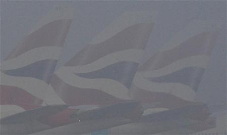 Tailfins of British Airways planes are just visible through the fog at Heathrow Airport in west London December 12, 2012. REUTERS/Toby Melville
