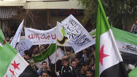 Demonstrators hold opposition flags during a protest against Syria's President Bashar al-Assad, in Jubar near Damacus January 18, 2013, in this picture provided by Shaam News Network. REUTERS/Abu Adel Al-Jubarani/Shaam News Network/Handout