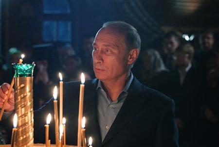 Russian President Vladimir Putin lights a candle during a Christmas eve service in an Orthodox Monastery in the south Russian city of Sochi January 7, 2013. REUTERS/Mikhail Klimentyev/RIA Novosti