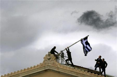 Parliament employees raise a mast after they replaced a torn-off Greek flag with a new one atop the parliament in Athens Syntagma (Constitution) square April 18, 2012. REUTERS/Yannis Behrakis
