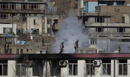 Forças de segurança afegãs correm no telhado da polícia de trânsito de Cabul durante ataque de insurgentes na capital afegã. 21/01/2013 REUTERS/Omar Sobhani