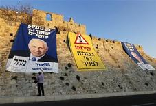 "A man stands next to campaign banners depicting Israel's Prime Minister Benjamin Netanyahu after Likud-Yisrael Beitenu activists draped them on walls surrounding Jerusalem's Old City January 20, 2013. Netanyahu said on Saturday a country with as many enemies as Israel cannot afford a weak ruling party, after polls ahead of Tuesday's parliamentary election showed a slide in his support. The banners read (L and C) ""Only Netanyahu will protect Jerusalem"" and ""Warning! '67 borders ahead"". REUTERS/Ronen Zvulun"