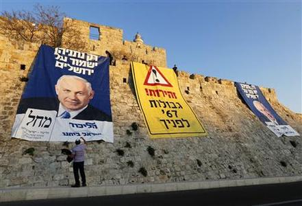 A man stands next to campaign banners depicting Israel's Prime Minister Benjamin Netanyahu after Likud-Yisrael Beitenu activists draped them on walls surrounding Jerusalem's Old City January 20, 2013. Netanyahu said on Saturday a country with as many enemies as Israel cannot afford a weak ruling party, after polls ahead of Tuesday's parliamentary election showed a slide in his support. The banners read (L and C) ''Only Netanyahu will protect Jerusalem'' and ''Warning! '67 borders ahead''. REUTERS/Ronen Zvulun