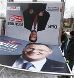La canciller alemana, Angela Merkel, lamentó el lunes que su partido perdiera las elecciones en Baja Sajonia, provocando la salida del gobierno de David McAllister en ese estado. En la imagen, un cartel electoral del líder democristiano y gobenador saliente del estado David McAllister y otro del ganador en Hanover, el 21 de enero de 2013. REUTERS/ Kai Pfaffenbach