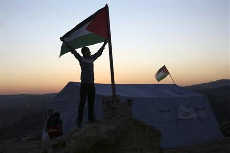 An activist holds a Palestinian flag placed near a newly-erected tent in the West Bank village of Beit Iksa, between Ramallah and Jerusalem January 20, 2013. REUTERS/Mohamad Torokman