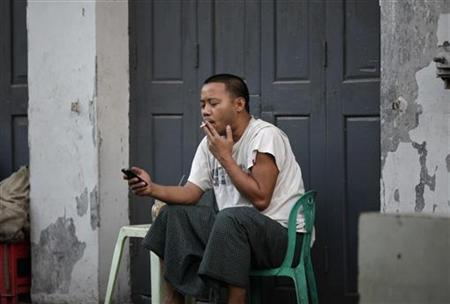 A man uses his mobile phone along a street in Yangon January 19, 2013. REUTERS/Soe Zeya Tun