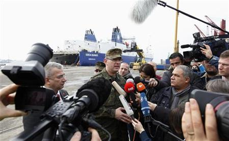 Wing Commander Colonel Marcus Ellermann (C) of the Surface to Air Missile (SAM) at the German armed forces Bundeswehr addresses the media as German military vehicles carrying equipment for NATO patriot defence missiles, disembark at Turkey's Mediterranean port of Iskenderun in Hatay province January 21, 2013. REUTERS/Umit Bektas